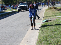An HU student clears leaves from a sidewalk near the North Phoebus Community Center.